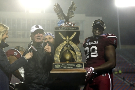 Dec 27, 2014; Shreveport, LA, USA; South Carolina Gamecocks head coach Steve Spurrier and defensive player of the game linebacker Jonathan Walton (28) hold the Independence Bowl trophy after defeating the Miami Hurricanes in the 2014 Independence Bowl at Independence Stadium. South Carolina defeated Miami 24-21. Mandatory Credit: Nelson Chenault-USA TODAY Sports